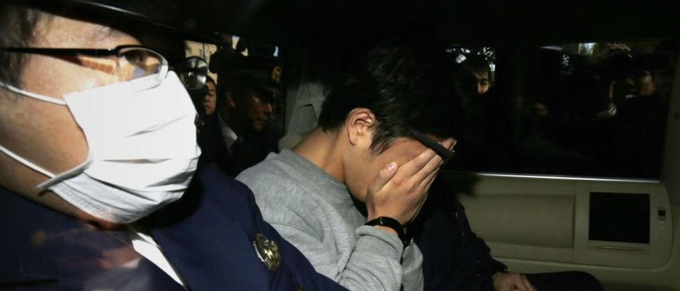 Suspect Takahiro Shiraishi (C) covers his face with his hands as he is transported to the prosecutor's office from a police station in Tokyo on November 1, 2017. The 27-year-old Japanese man, who was arrested after police found nine dismembered corpses rotting in his house, has confessed to killing all his victims over a two-month spree after contacting them via Twitter, media reports. (Photo: STR/AFP/Getty Images)