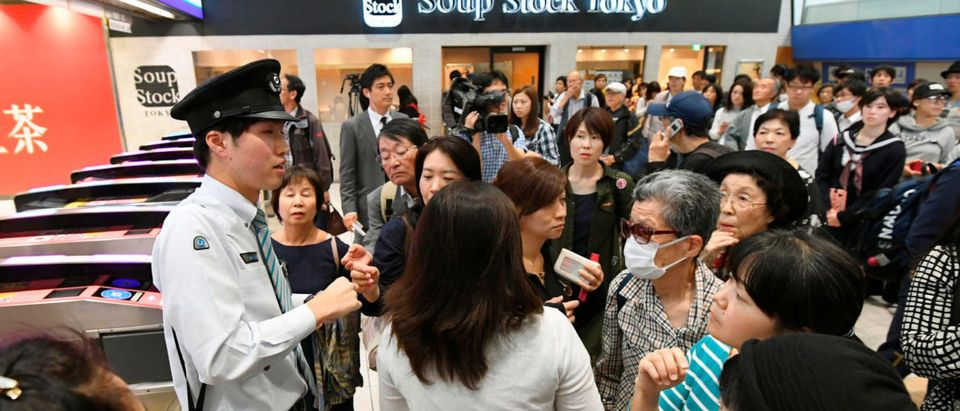 Passengers gather around a railway company staff as they try to gather information after train services were suspended because of a power outage, caused by a fire at an underground cable facility, at a station in Tokyo