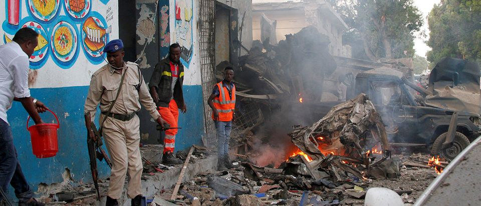 Somali security officers secure the scene of a suicide car bomb explosion, at the gate of Naso Hablod Two Hotel in Mogadishu