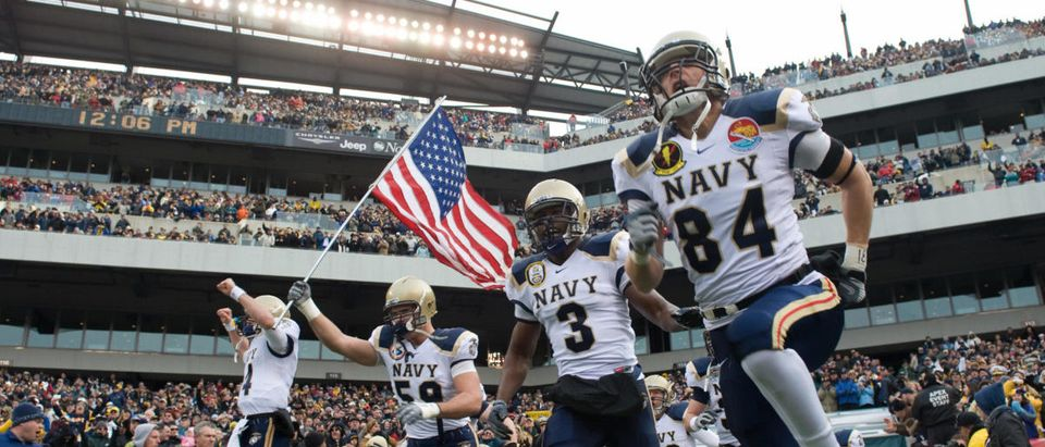 Members of the Navy football team run ou