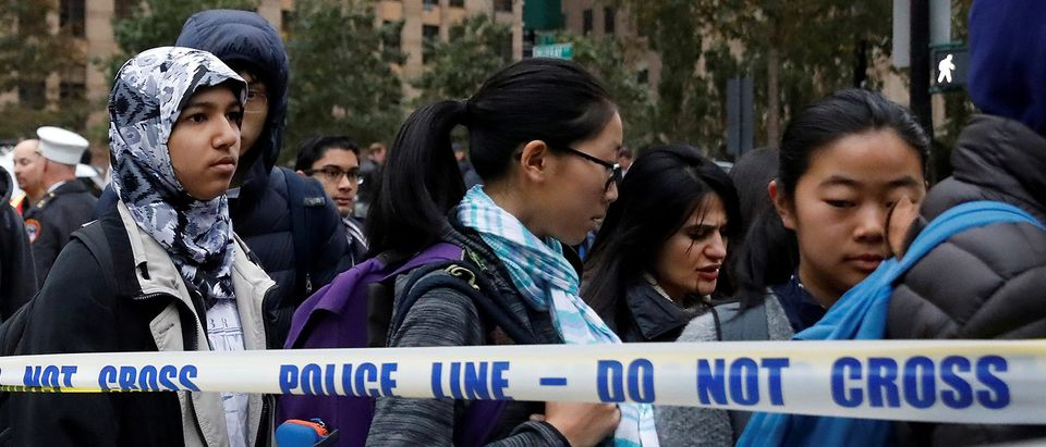 Students walk past police line tape on their way to school a day after a man driving a rented pickup truck mowed down pedestrians and cyclists on a bike path alongside the Hudson River in New York City