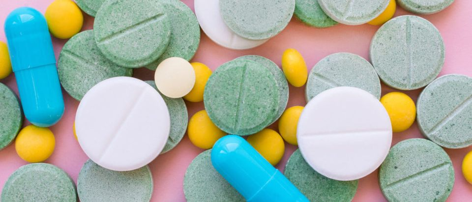 Opioid Pills. Opioid epidemic and drug abuse concept. Different tablets, pills, capsule on a pink background. Heap mix therapy drugs. By Iryna Imago