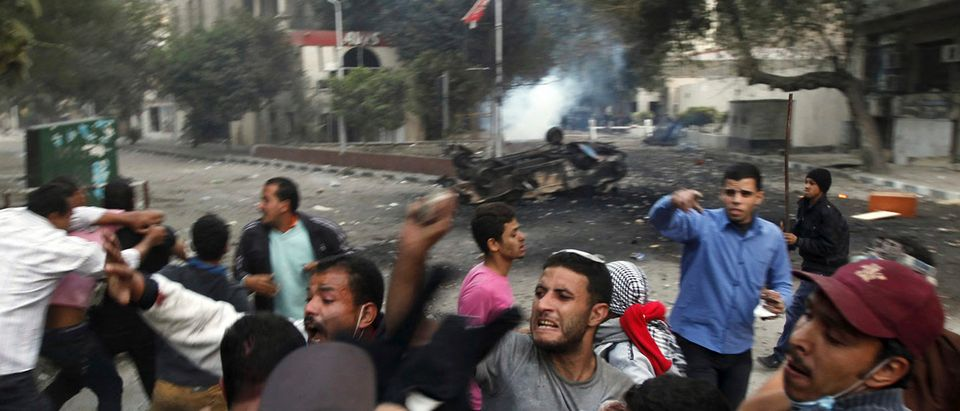 Protesters hit riot policemen after they caught hold of them during clashes in front of the U.S. embassy, near Tahrir Square in Cairo
