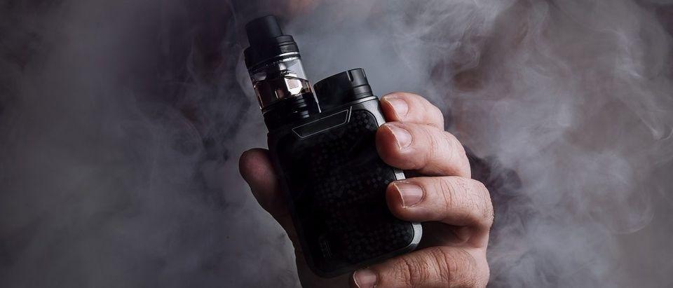 Man holds e-cigarette mod in cloud of vapor. Credit: Shutterstock/joseluisserranoariza