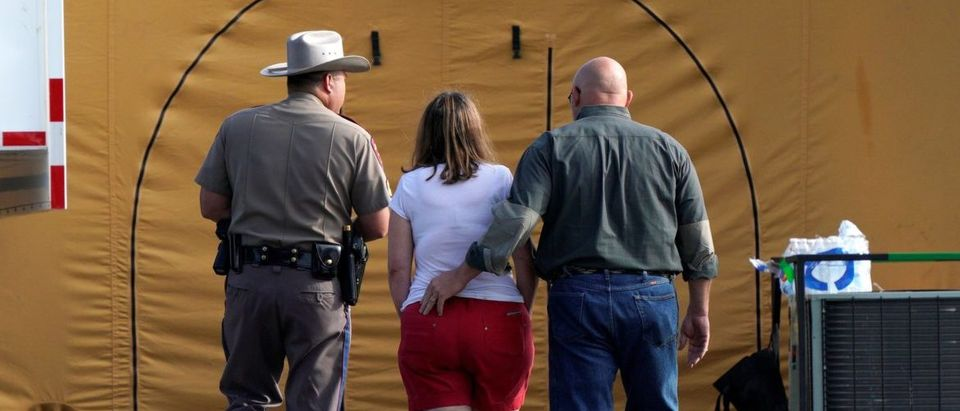 A woman is escorted to site of a shooting at the First Baptist Church of Sutherland Springs, Texas, U.S. November 6, 2017. REUTERS/Rick Wilking