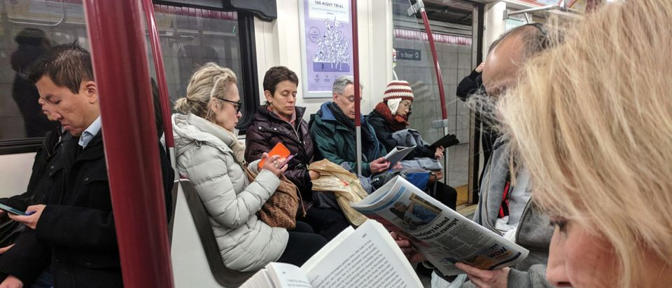 Morning commuters read while riding the TTC Subway in Toronto,