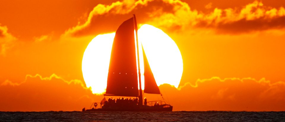 A sail boat passes in front of the sun as the last rays of sunlight of 2011 hit the waters off Waikiki Beach in Honolulu