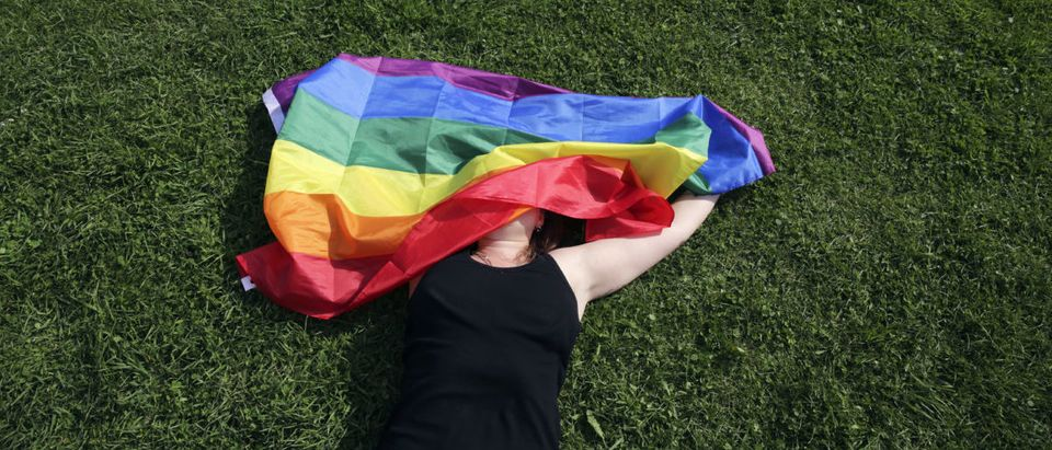 """A woman with a rainbow flag lays on grass during the LGBT (lesbian, gay, bisexual, and transgender) community rally """"VIII St.Petersburg Pride"""" in St. Petersburg, Russia August 12, 2017. REUTERS/Anton Vaganov A woman with a rainbow flag lays on grass during the LGBT (lesbian, gay, bisexual, and transgender) community rally """"VIII St.Petersburg Pride"""" in St. Petersburg, Russia August 12, 2017. REUTERS/Anton Vaganov"""