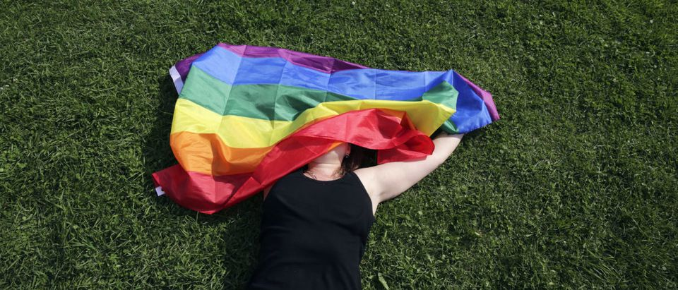 "A woman with a rainbow flag lays on grass during the LGBT (lesbian, gay, bisexual, and transgender) community rally ""VIII St.Petersburg Pride"" in St. Petersburg, Russia August 12, 2017. REUTERS/Anton Vaganov"