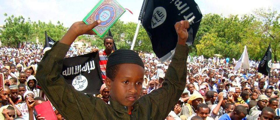 A Somali boy holds a copy of the Koran as he stands near al-Shabaab flags during a protest against the burning of the Islamic holy book at southern Mogadishu?s main stadium, September 15, 2010. Thousands of Muslim faithful took part in the protest, days after plans by obscure U.S. Pastor Terry Jones, which he later abandoned, to burn copies of the Koran to mark the anniversary of the September 11, 2001, hijacked airliner attacks on the United States. (Photo: REUTERS/Omar Faruk)
