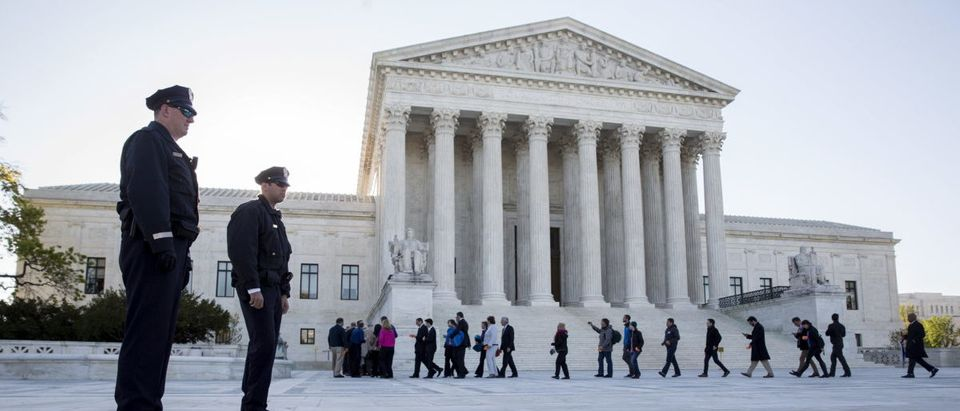 Police watch as members of the public enter the Supreme Court before the court hears arguments about gay marriage in Washington April 28, 2015. The nine justices will be hearing arguments concerning gay marriage restrictions imposed in Kentucky, Michigan, Ohio and Tennessee, four of the 13 states that still outlaw such marriages. REUTERS/Joshua Roberts