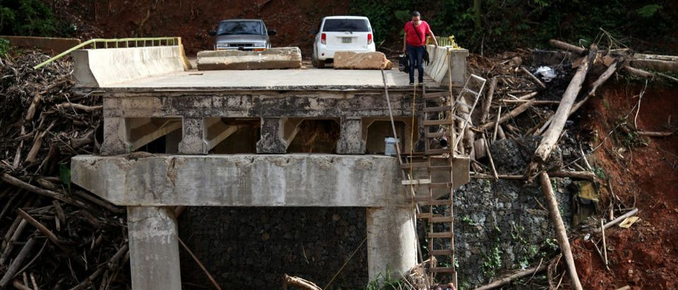 A woman looks as her husband climbs down a ladder at a partially destroyed bridge, after Hurricane Maria hit the area in September, in Utuado, Puerto Rico November 9, 2017. Picture taken November 9, 2017. REUTERS/Alvin Baez