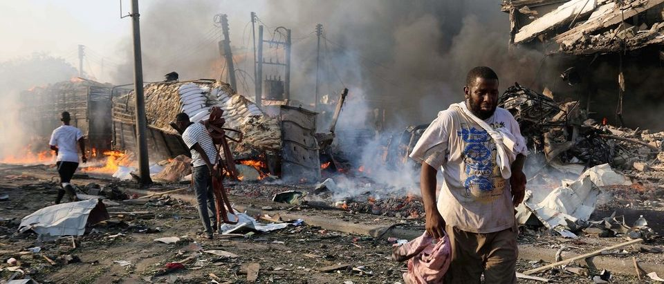 Civilians walk at the scene of an explosion in Mogadishu
