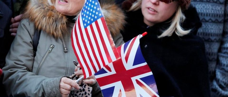 People hold U.S. and British flags as they wait for Britain's Prince Harry and his fiancee Meghan Markle to attend an event in Nottingham