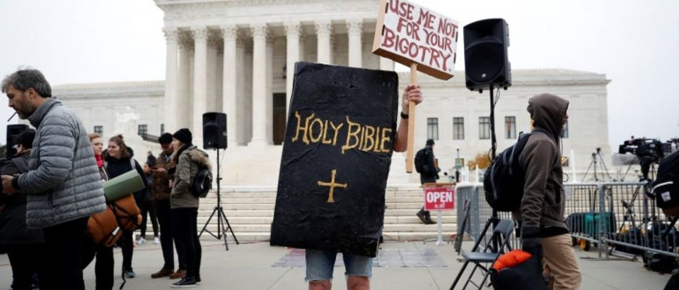 A demonstrator protests ahead of oral arguments in the Masterpiece Cakeshop v. Colorado Civil Rights Commission case at the Supreme Court in Washington