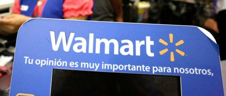 FILE PHOTO: Cashier smiles beyond a Walmart logo during the kick-off of the 'El Buen Fin' (The Good Weekend) holiday shopping season, at a Walmart store in Monterrey