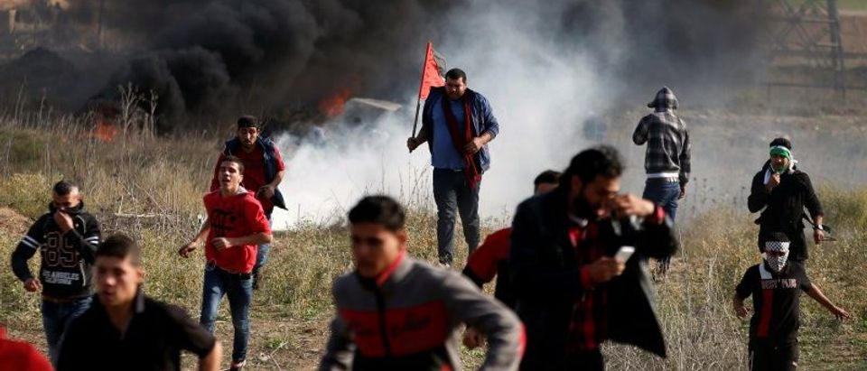 Palestinian protesters run for cover during clashes with Israeli troops near the border with Israel in the east of Gaza City