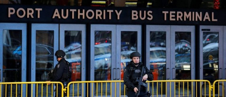 Police officers stand guard outside the New York Port Authority Bus Terminal in New York City after reports of an explosion
