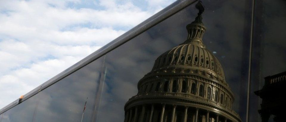 The Capitol Dome is reflected in the window of a bus departing to the White House with members of congress for a bill passage event after the Republicans passed a tax bill at Capitol Hill in Washington