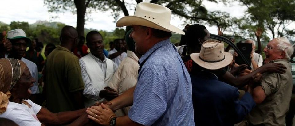 Commercial farmers Rob Smart and his son Darreyn are welcomed at Lesbury Estates by village elders and children at a farm in Headlands communal lands east of the capital Harare