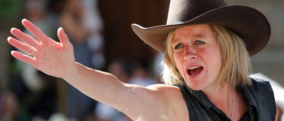Alberta Premier Notley waves at spectators during the Calgary Stampede Parade in Calgary.