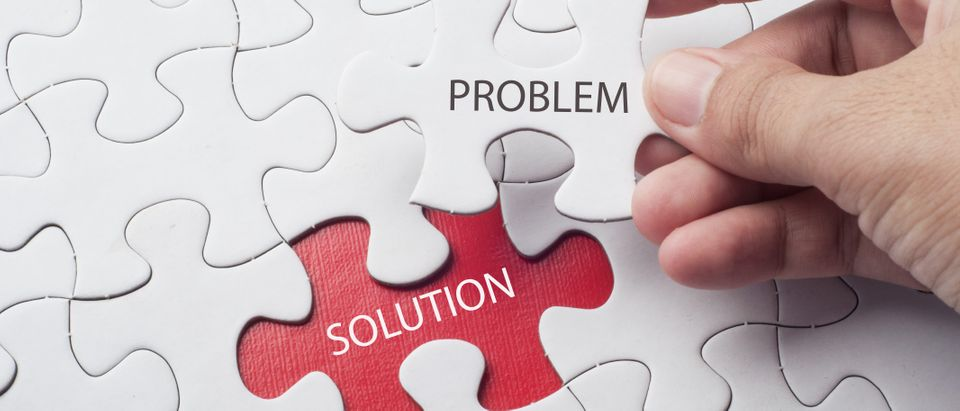 Hand holding piece of jigsaw puzzle with word problem & solution