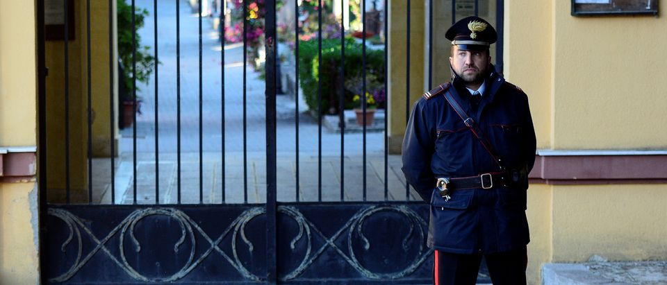 An Italian Carabinieri police officer patrols outside the cemetery in Corleone