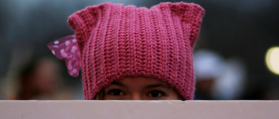 A woman wearing pink pussy protest hat poses for a photograph during the Women's March on Washington, following the inauguration of U.S. President Donald Trump, in Washington