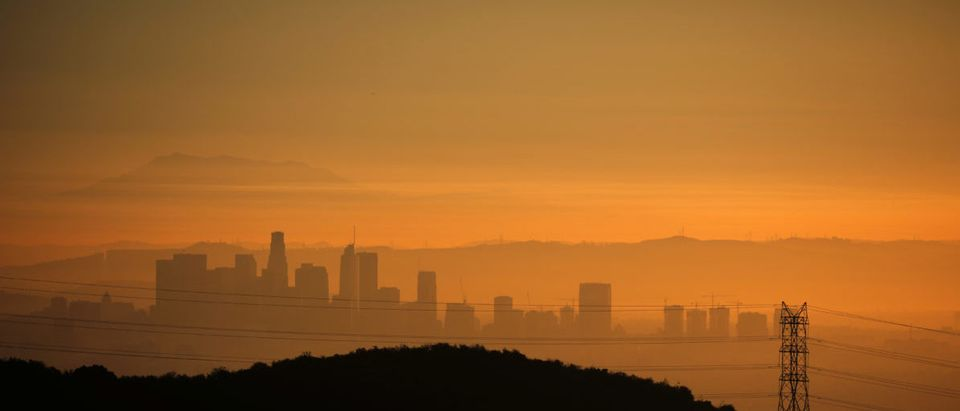 The downtown Los Angeles skyline is seen behind an electricity pylon at sunrise in Los Angeles