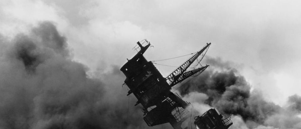 The forward superstructure of the sunken battleship USS Arizona burns after the Japanese raid on Pearl Harbor. (Photo credit: U.S. Navy/U.S. Naval History and Heritage Command/Handout via Reuters)