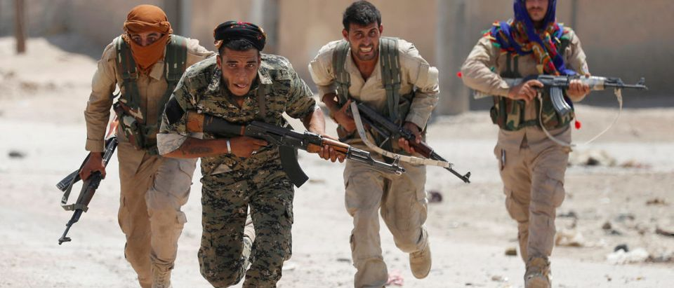 """Kurdish fighters from the People's Protection Units (YPG) run across a street in Raqqa, Syria, July 3, 2017. Goran Tomasevic: """"They were members of Kurdish YPG militia. They were running across the street because ISIS fighters' positions were nearby. I shot the picture in a last day of my assignment. I was lucky to have that picture as YPG fighters were giving very restricted access to media."""" REUTERS/ Goran Tomasevic/File Photo"""