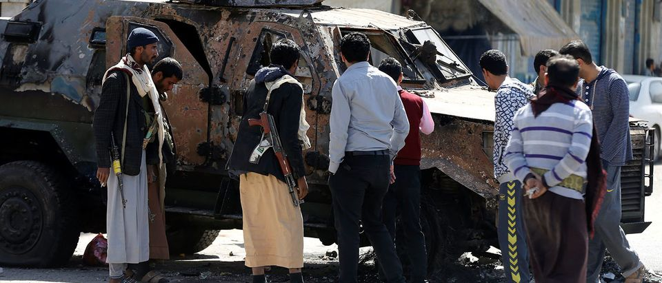 Houthi fighters and people look at an armored personnel carrier damaged by recent clashes with forces loyal to Yemen's former president Ali Abdullah Saleh in Sanaa, Yemen