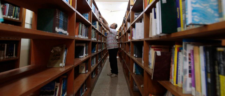 """An Iraqi librarian sorts books on the shelves of the central library in Basra, about 420 km (261 miles) southeast of Baghdad, March 18, 2013. Ten years ago this week, British forces entered Iraq's second city, Basra, as part of the U.S.-led invasion of the country. Known locally as a cultural hero, librarian Alia Baqer moved to rescue the contents of Basra's central library before everything was lost. """"At the beginning of the war on Iraq, the governor (of Basra) took the library over as a headquarters for himself and his guards, mounting machine guns on top of the building. So, we asked the governor if we could take the important books to our homes, but he rejected the idea. Eventually we took the responsibility ourselves to transfer the books, without the governor's approval,"""" Baqer said. Baqer moved about 30,000 books out of the city's central library to a neighbouring restaurant and later to her home, before the looting and burning of the library during the first days of the U.S.-invasion of Iraq began. REUTERS/Atef Hassan"""