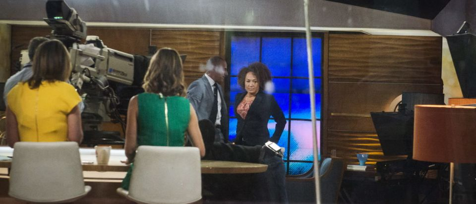 """Host Matt Lauer (C) walks past Washington state civil rights advocate Rachel Dolezal (R) ahead of an interview in the NBC's """"Today"""" show studios in Manhattan, New York on June 16, 2015. Dolezal, who has been accused of falsely claiming she is African-American, said on Tuesday she identifies as black. Dolezal, who resigned on Monday as president of the Spokane chapter of the National Association for the Advancement of Colored People, said in an interview on NBC's """"Today"""" show that her identity was """"not some freak ... mockery black-face performance."""" REUTERS/Stephanie Keith"""
