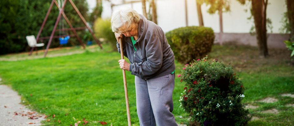 Old lady with broom (Shutterstock)