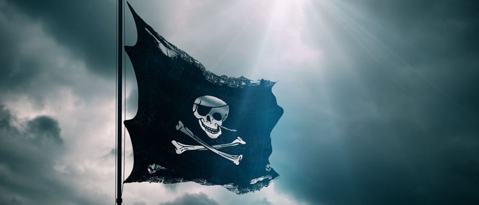 ripped tear grunge old fabric texture of the pirate skull flag waving in wind, calico jack pirate symbol at cloudy sky with sun rays light, dark mystery style, hacker and robber concept Shutterstock/ donfiore