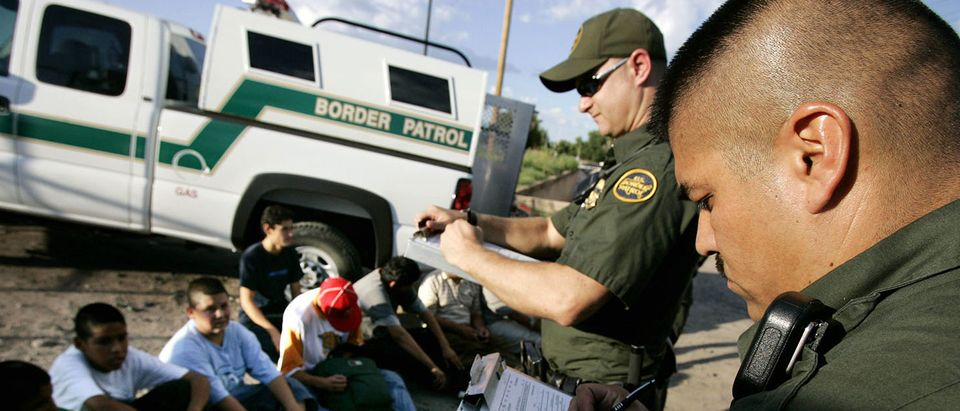 U.S. Border Patrol agents, David Macias (R) and Kurt Dannawitz, process a group of illegal aliens Aug. 30, 2005 in Nogales, Arizona. (Photo by Sandy Huffaker/Getty Images)