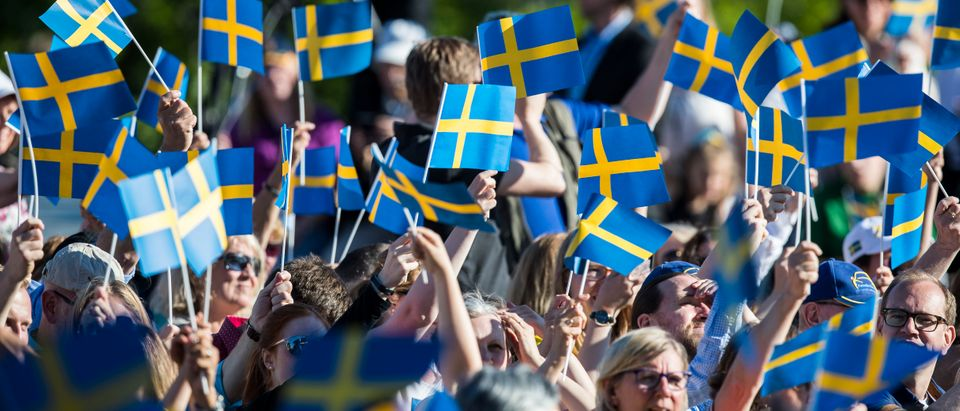 STOCKHOLM, SWEDEN - JUNE 06: Spectators wave the Swedish flag during the national day celebrations at Skansen on June 6, 2017 in Stockholm, Sweden. (Photo by Michael Campanella/Getty Images)