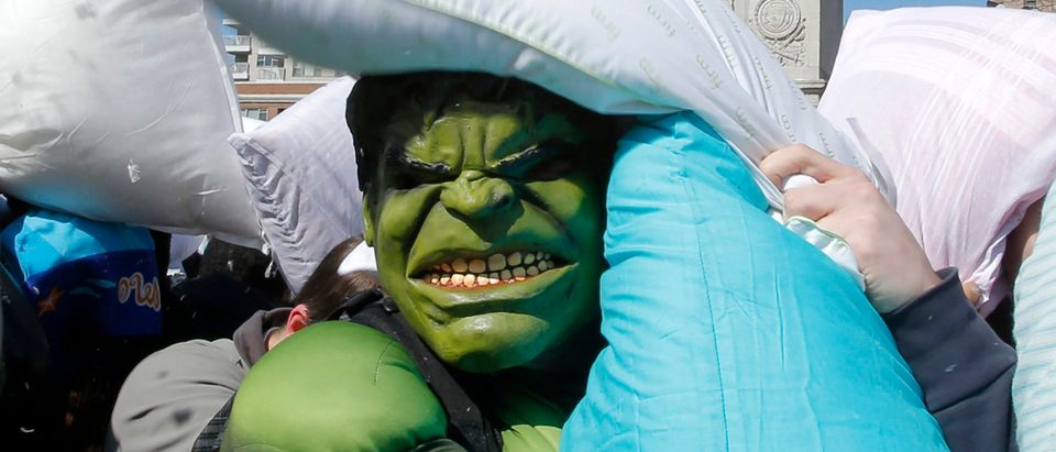 A man wearing a Hulk mask is hit by pillows during International Pillow Fight Day in New York