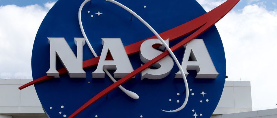 NASA sign at Cape Canaveral, Kennedy Space Center with blue cloudy sky background.