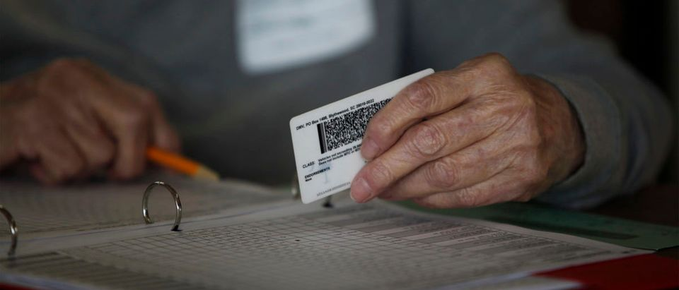 A precinct worker checks a voter ID at the Bermuda precinct for the 2016 Presidential election in Dillon