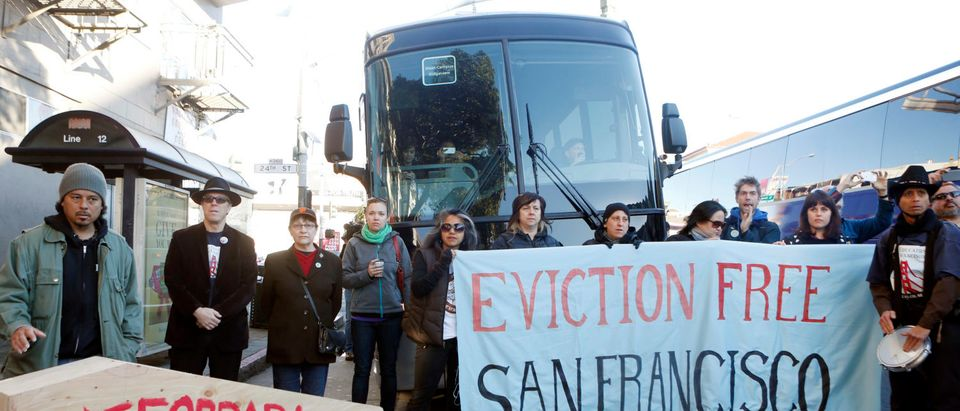 Protesters block a bus full of Apple employees during a protest against rising costs of living in San Francisco