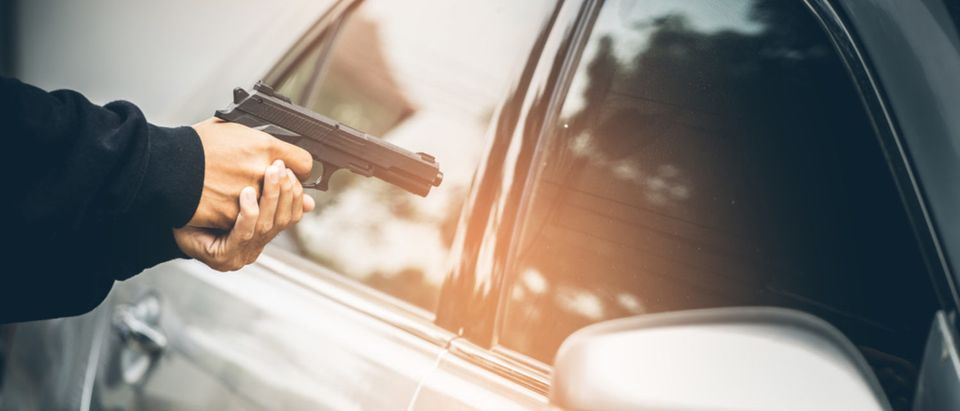 Armed man shoots woman driver after a fender bender and fit of road rage. [Shutterstock - Chayantorn Tongmorn]