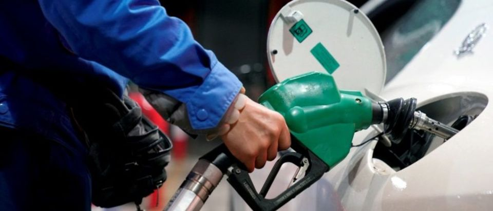FILE PHOTO: A gas station attendant pumps fuel into a customer's car at a gas station in Shangha