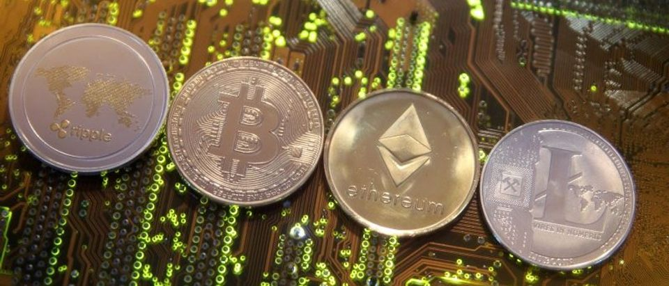 FILE PHOTO:Representations of the Ripple, Bitcoin, Etherum and Litecoin virtual currencies are seen on motherboard in this illustration picture