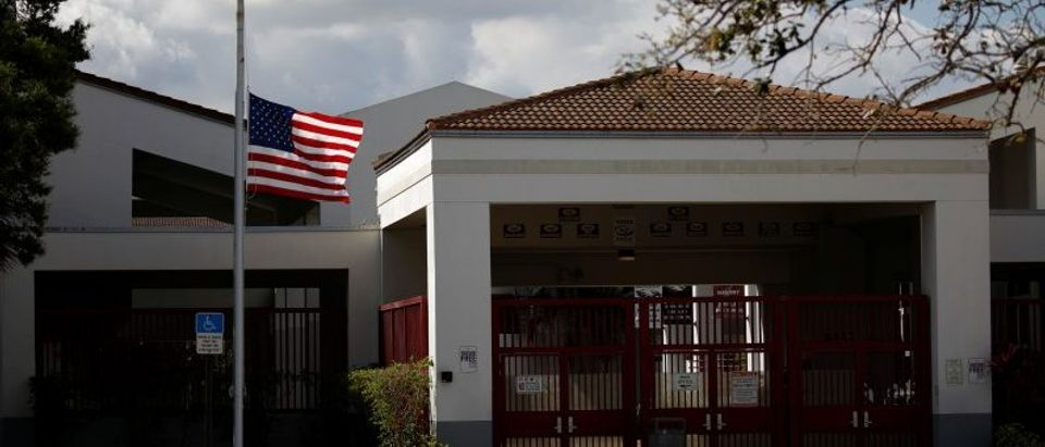 A flag flies at half mast next to the entrance of the Marjory Stoneman Douglas High School, after the police security perimeter was removed, following a mass shooting in Parkland