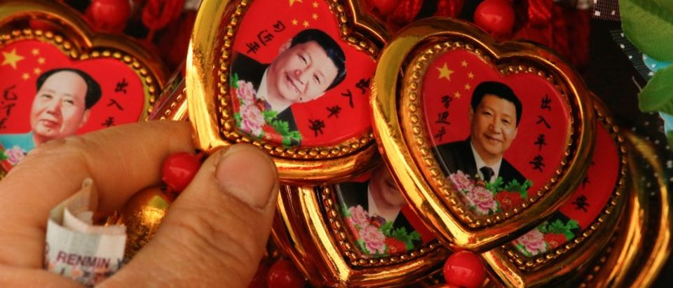 FILE PHOTO: A woman picks a souvenir necklace with a portrait of Chinese President Xi Jinping from a selection that also includes necklaces featuring late Chinese Chairman Mao Zedong at a stall in Beijing