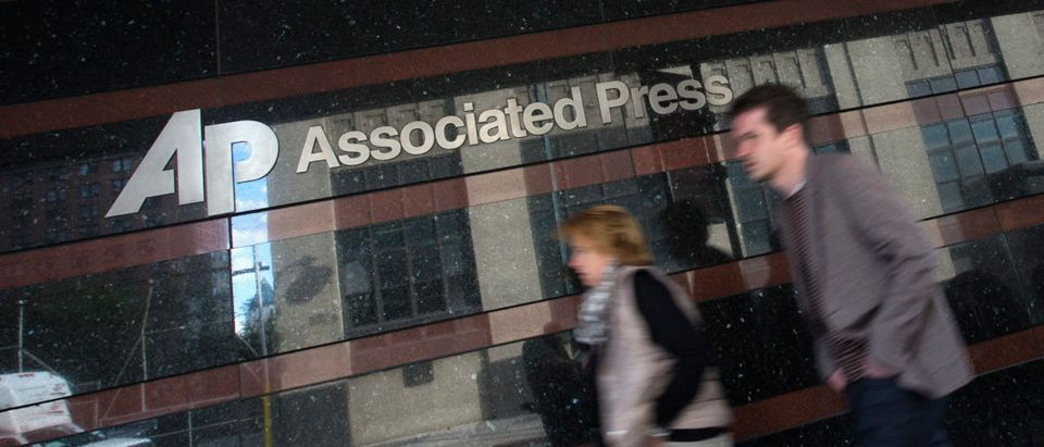 A couple walk past the offices of the Associated Press in Manhattan, New York