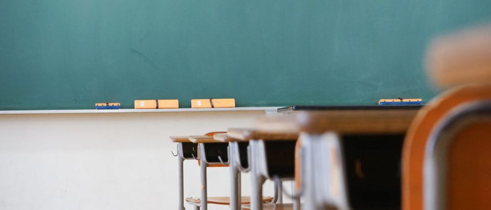 Pictured is a classroom complete with desks and a blackboard. (Shutterstock/maroke)
