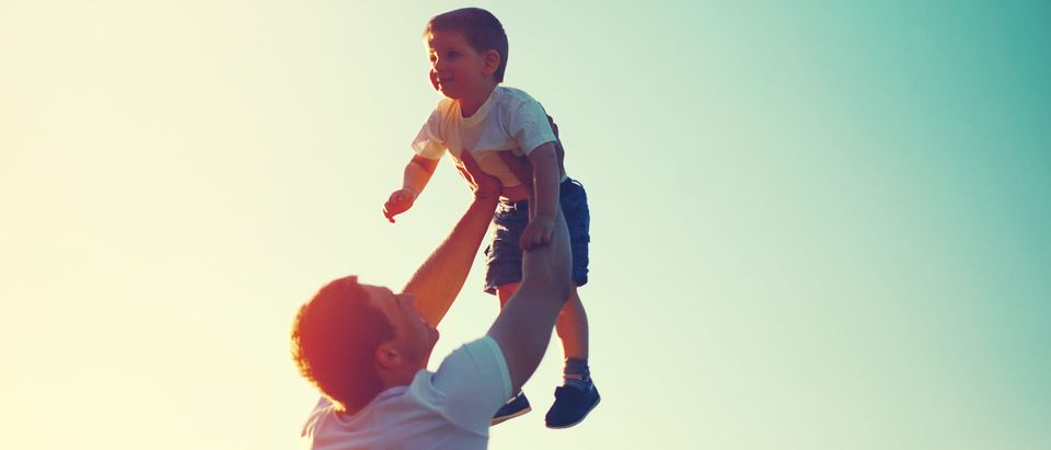 A father holds up his son. (Shutterstock)